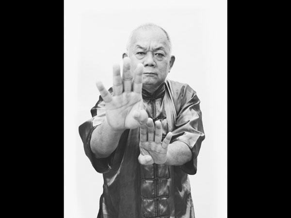 Bald man, hands toward camera